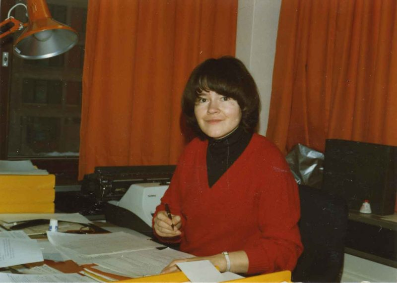 Liisa Kauppinen, the Secretary of the organization for the deaf in Helsinki, seated by a desk.